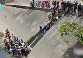 委内瑞拉全国大停电,民众从下水道取水